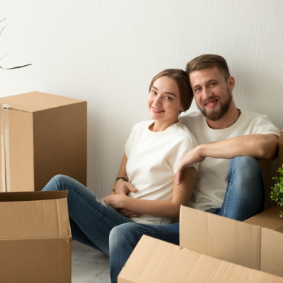 New Canaan Connecticut couple sits amoung moving boxes after buying their first home and insurance.