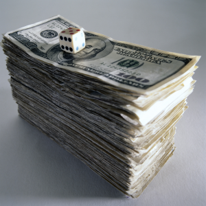 A die sitting atop a stack of money representing the gamble that clients sometimes take in choosing to self-insure their home or business in Darien, Connecticut.