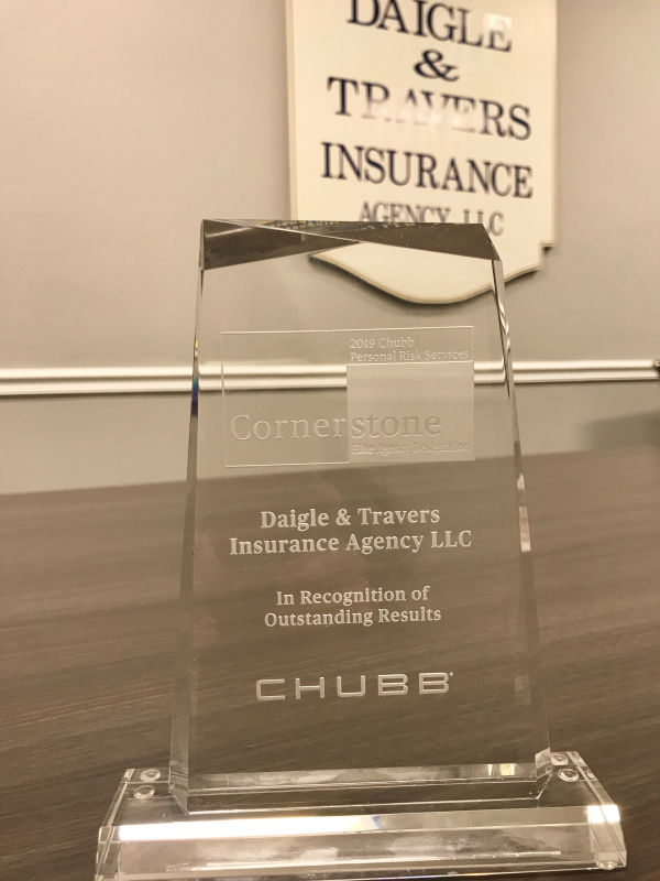 Chubb Cornerstone Award in front of Daigle & Travers Insurance Agency sign.
