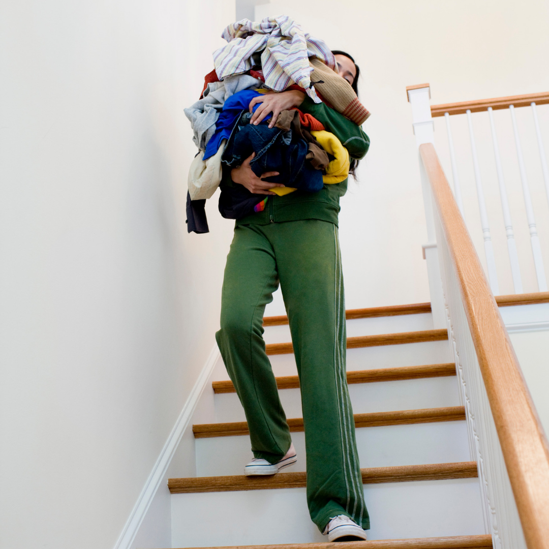 Domestic worker carrying too much laundry down the stairs