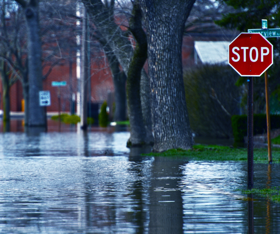 Flooded street with stop sign, one way sign and Riverview Street sign in Westport CT.