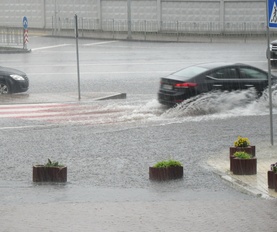 Car caught in flash flood driving down road as waves splash up from tires.
